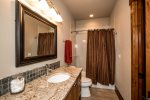 A tub shower condo and granite counter tops in the queen rooms bathroom.