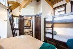 The upper loft bedroom sleeps 4 in a king and two bunks, with a private bathroom