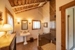 The bathroom features beautiful wood, tile and stonework