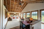 The living room is light and airy with soaring log ceilings and beautiful views out every window