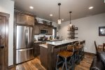 The kitchen features band new stainless steel appliances.