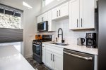 The beautiful tile backsplash and white cabinets and counters make things bright