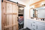 The bathroom has a sliding barn door for privacy and double vanity