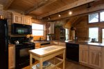 The black appliances work well with the wood cabinets, island, and ceiling beams.