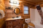 The bathroom vanity resembles an old ice box with its oversized hinges. There is a bathtub/shower combo in the full bath.