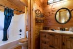 The upper level bathroom has a cabinet similar to the vanity below and a bathtub/shower combination.