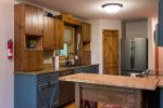 Just beyond the dining area is the kitchen with all of the necessities including a stainless French Door refrigerator with bottom drawer freezer.
