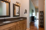 The adjoining full bathroom has a vanity with a double sink and plenty of storage.