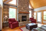 The focal point of the great room is the beautiful stone fireplace gas logs that is flanked by large windows that reach to the peak of the two-story room.