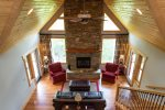 From this loft view, you can see the beauty of the fireplace, tall windows, and beautiful wood ceiling.