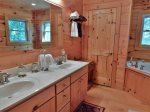 The adjoining full bath has a double vanity, walk-in shower not pictured, and a jetted tub.