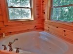 The jetted corner tub is a perfect spot to relax and, with two windows, you can take in the view.