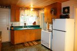 Kitchen is equipped with an electric range, drip coffee pot, toaster, microwave and full size fridge.