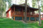 Spacious cabin with a large deck, equipped with a propane grill and plenty of seating.