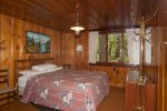 Master bedroom has a queen bed with a window viewing the beautiful woods nearby.