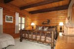 Master bedroom has a king bed with a window viewing the beautiful woods nearby.