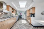 Kitchen Features Viking Appliances, Large Skylight and Booth Seating For Four