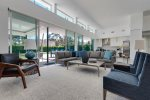 Formal Living Room Features 74 Inch TV, Ample Seating and Walls of Glass Overlooking the Pool