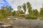 Rear of home seen from across La Plata River at Durango Colorado waterfront vacation rental cabin river pond fly fishing canoe Hesperus CO