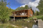 Durango Colorado waterfront vacation rental cabin river pond fly fishing canoe Hesperus CO diversion stream and footbridge at rear of home