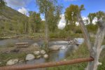 View of La Plata River from main deck at Durango Colorado waterfront vacation rental cabin river pond fly fishing canoe Hesperus CO