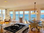 Open concept Kitchen / living/ dining with walls of windows and doors leading to the waters edge deck