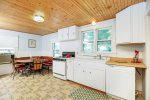 Huge Country Kitchen with warm wood ceiling and seating for 6 at the Dining Table.