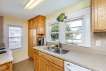 The Kitchen has Solid Surface Countertops and Warm Wood Cabinetry.