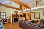 Vaulted ceiling in living room with plenty of seating and flat screen TV