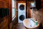 Main level half bath with stacked washer and dryer