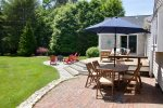 Outdoor dining with umbrella, lounge seating, fire pit with Adirondacks