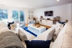 Living room with large sectional sofa, flatscreen tv and plenty of seating