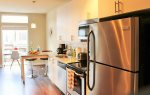The kitchen is efficient, with top-of-the-line stainless steel appliances, and roomy cabinets lending to its spacious feel.