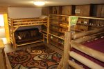 The downstairs bunk room includes a double-queen bunk two queen beds, plus a twin-futon bunk. Check out the toy wall