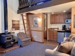 Living area, wood stove, loft access