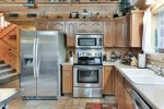A fully supplied kitchen will allow you to make homecooked meals at Black Bear Cabin.