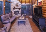 Outdoor screened in porch with fireplace and large flat panel TV