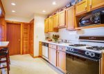 Fully applianced galley kitchen with breakfast bar.