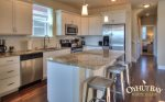 open concept fully furnished kitchen with island bar and 3 stools