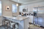 open concept fully furnished kitchen with stainless appliances, island bar with 3 stools