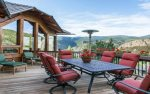 Outdoor table, loungers, heat lamp, and grill occupy the upper level deck and balcony.