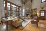 Great room with large fireplace, floor to ceiling windows, and ample seating