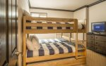 5th bedroom with two sets of twin bunks sleeps 4, flat-screen television, and en-suite bathroom.