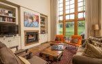 Great room with gas fireplace, flat screen TV, and floor to ceiling windows