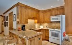 Fully equipped kitchen with breakfast bar seating for four.