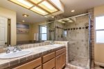 A bigger bathroom with two sinks and shower.