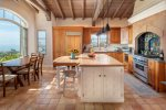 Abundant sunlight illuminates gourmet kitchen with cathedral ceiling and spectacular views