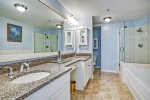Master bath has large bathtub, walk-in glass enclosed shower and twin vanities.