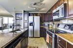 Kitchen has ample kitchenware, high-end appliances and breakfast bar.