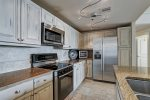 Kitchen is spacious with stainless steel appliances, granite counters.